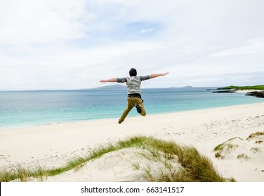 Young model jumping on a sand dune with open arms. White sandy beach and blue sky in the background. Isle of Lewis, Hebrides, Scotland, UK.