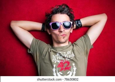 Young model making strange faces on red background, wearing purple sunglasses. isolated