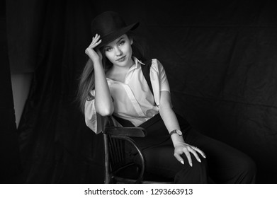 Young model posing in a man's suit and hat. Charlie Chaplin style clothing with suspenders blackwhite