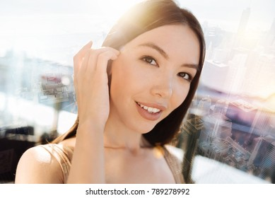 Young model. Pretty female person keeping smile on her face and touching hear while looking forward
