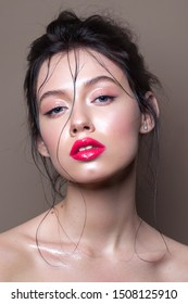 Young model with professional makeup, perfect skin, wet hairdo. Glossy eyelids and glossy red lips.