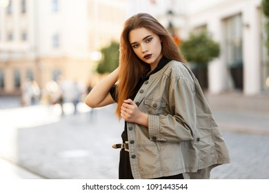 Young model woman with make-up in a fashionable jacket posing in the city