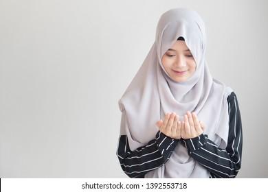 young modern asian muslim woman with islamic prayer hand; concept of Ramadan, Eid al Fitr, meditation, islamic praying, islam festival, muslim religious activities