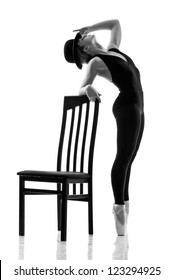 Young modern ballet dancer posing near the chair. Isolated on a white background