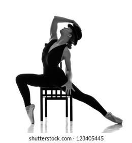 Young modern ballet dancer posing on the chair. Isolated