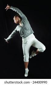 young modern ballet dancer posing on black background