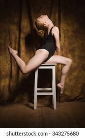 Young modern ballet dancer posing in dark interior