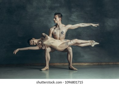 The young modern ballet dancers with tatoos on bodys posing on gray studio background