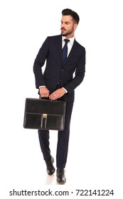 young modern business man holding suitcase with both hands and looks to side on white background