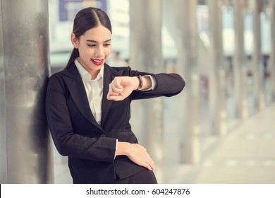 Young modern business woman looking on watch with copy space