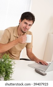 Young modern businessman with cup of coffee sitting at the office