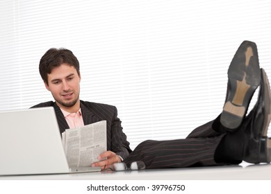 Young modern businessman with laptop and newspaper sitting at the office