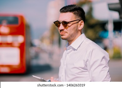 Young modern businessman is outside, walking in the city while looking around, calling for a taxi ride, e-hailing