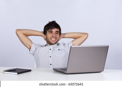 Young modern businessman relaxing at his office happy with his work