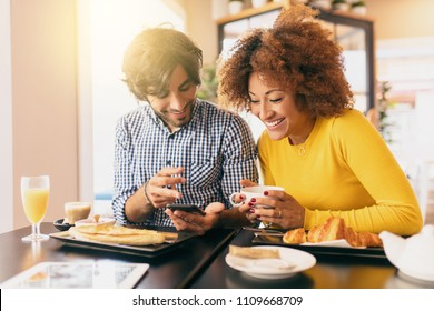 Young modern couple at cafe, she is drinking a tea and he is drinking a coffee, he is showing her something funny in his mobile phone. They are happy and feel comfortable.