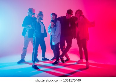 Young modern dancing group of five adult young people practice dancing on colorful background. Fashionably dressed youngsters posing over blurred disco club color lights