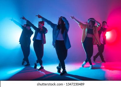Young modern dancing group of six adult young people practice dancing on colorful background
