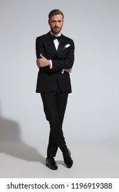 young modern elegant man in tuxedo standing with hands and leg crossed on grey studio background