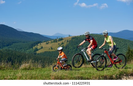 Young modern family tourists bikers, mom, dad and child riding on bicycles on grassy hill. Carpathian mountains, blue summer sky on background. Active lifestyle, traveling and happy relations concept.