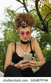 Young modern girl is using the phone. Eccentric girl with curly hair hair is using the phone surrounded by nature. Using technology outdoor.
