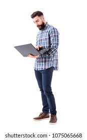 Young modern handsome bearded worker holding and using laptop computer. Full body isolated on white background.