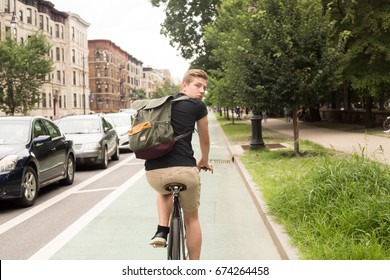 Young modern hipster man riding bike looking back, photographed in Brooklyn NY in July 2017