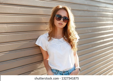 Young modern hipster woman in stylish sunglasses in a summer fashion white t-shirt in trendy jeans is standing near a wooden vintage wall on a sunny spring day. Cute girl resting outdoors.
