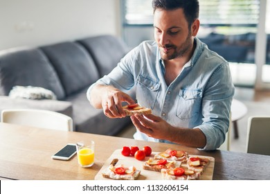 Young modern man eating sandwiches at home