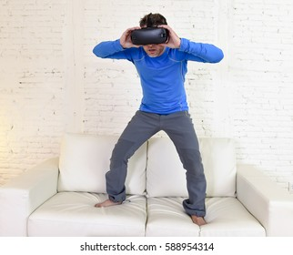 young modern man at home standing on living room sofa couch excited using 3d goggles watching 360 virtual reality vision enjoying the fun cyber experience in vr simulation reality concept