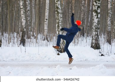 Young modern man slipped his body lost balance during walk go from birch grove in winter town. Freeze frame while jumping out and waving hands up before falling over snow. side skid boot has hazard.