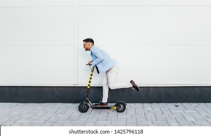 Young modern man using and driving electric scooter on city street. Modern and ecological transportation concept.