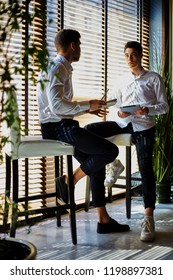 Young modern men sitting on stools in contemporary interior with notepad and tablet and talking