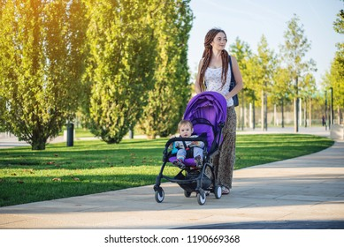 Young modern mom with baby son in stroller walking in Sunny Park. The concept of the joy of motherhood and autumn mood