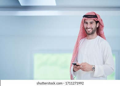 young modern muslim arabian businessman wearing traditional clothes while using smartphone at home