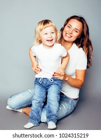 young modern smiling blond mother with little cute daughter on w