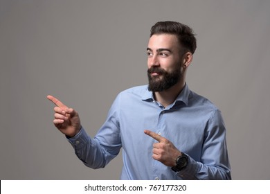 Young modern stylish bearded millennial business man showing fingers presenting blank copyspace against gray background.