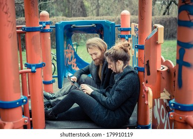 young modern stylish couple using tablet outdoors