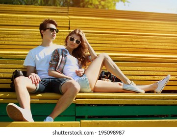 Young modern stylish hipsters couple rest on the bench in city park, sunny portrait couple teenagers in summer day