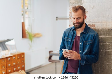 A young, modern, stylish man texting on a smart phone while leaning on a wall at home.