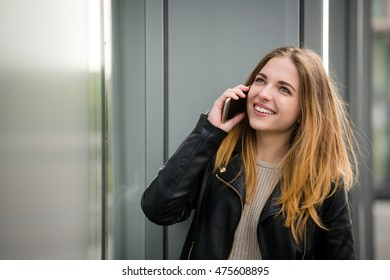 Young modern woman calling phone outdoor in street standing at shop window