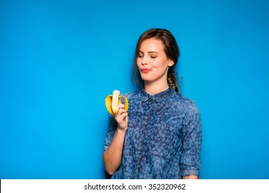 young modern woman eating a banana in hands on blue background
