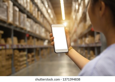 Young modern woman using touch screen mobile phone in warehouse storage. Asian girl hold cell phone order shopping product with smartphone, management stock online service business concept.