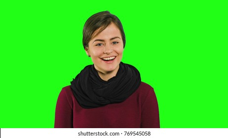 A young modest lady smiling and looking down against a green background. Medium shot