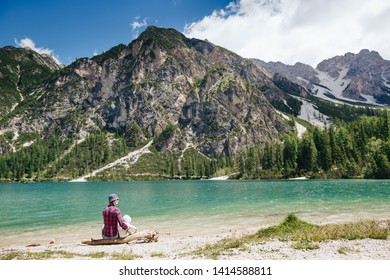 Young mom with baby boy travelling with backpack. Mother on hiking adventure with child, family trip in mountains. Vacations journey with infant Lago di Braies, Dolomites Mountains, Italy