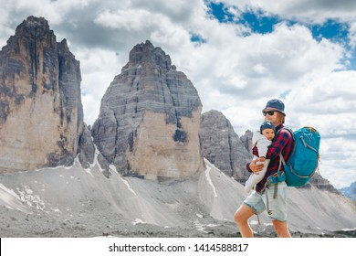 Young mom with baby boy travelling with backpack. Mother on hiking adventure with child, family trip in mountains. Vacations journey with infant National Park Tre Cime di Lavaredo, Dolomites, Italy