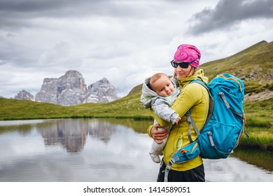 Young mom with baby boy travelling with backpack. Mother on hiking adventure with child, family trip in mountains. Vacations journey with infant, Dolomites Mountains, Italy