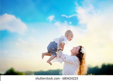 Young mom with baby to have fun in the wheat field