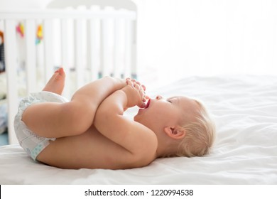 Young mom, changing baby diaper after bath in sunny bedroom