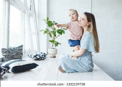 Young mom and cheerful adorable tot boy playing, having fun together at home on white wooden floor, mother playfully сalling and asking his son to take first steps. Mom and kid enjoying leisure time
