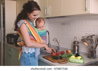 Young mom cooking in the kitchen with the little baby in a sling. Vegetarian healthy food. Healthy food breastfeeding mothers.